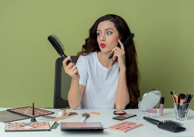 Nachdenkliches junges hübsches mädchen, das am make-up-tisch mit make-up-werkzeugen sitzt, die kämme halten, die gesicht damit berühren und einen von ihnen lokalisiert auf olivgrünem hintergrund betrachten