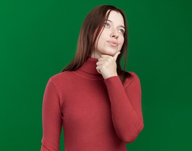 Nachdenkliches junges hübsches mädchen, das die hand am kinn hält und die seite isoliert auf grüner wand mit kopienraum betrachtet