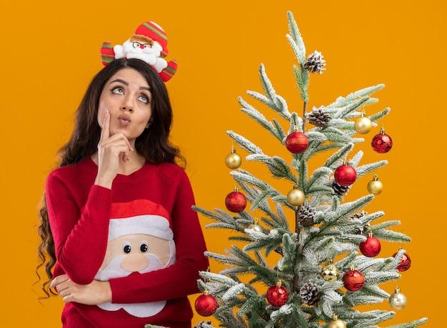 Nachdenkliches junges hübsches mädchen, das weihnachtsmann-stirnband und pullover trägt, die nahe verziertem weihnachtsbaum stehen und hand auf kinn halten, das lokal auf orange hintergrund schaut