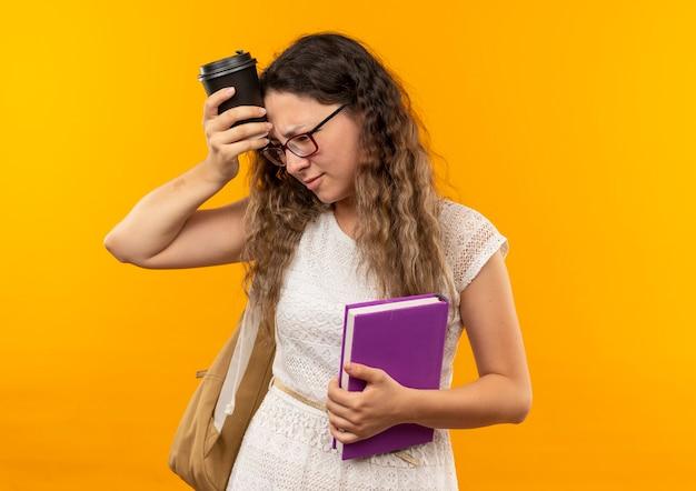 Nachdenkliches junges hübsches schulmädchen, das brille und rückentasche hält buch hält, das den seitenberührungskopf mit plastikkaffeetasse lokalisiert auf gelber wand betrachtet
