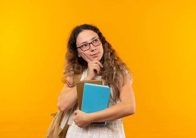 Nachdenkliches junges hübsches schulmädchen, das brille und rückentasche hält bücher hält, die hand auf kinn setzen und seite betrachten, die auf gelber wand lokalisiert wird