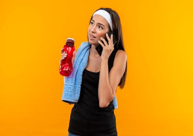 Nachdenkliches junges hübsches sportliches mädchen, das stirnband und armband trägt, das am telefon spricht, das seite hält wasserflasche mit handtuch auf schulter lokalisiert auf orange raum