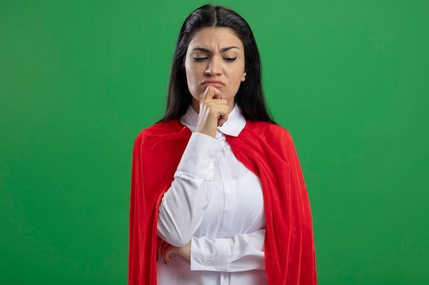 Nachdenkliches junges kaukasisches superheldenmädchen, das hand auf ellbogen und auf kinn hält, das lokalisiert auf grüner wand mit kopienraum schaut