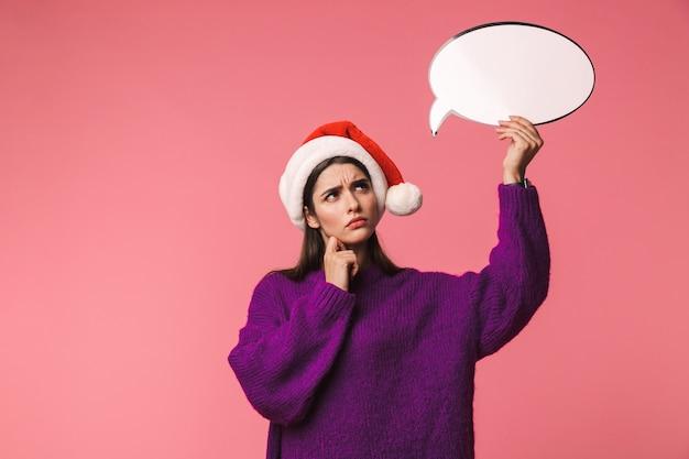 Nachdenkliches junges mädchen, das rote weihnachtsmütze trägt, die lokal über rosa steht und leere sprechblase hält