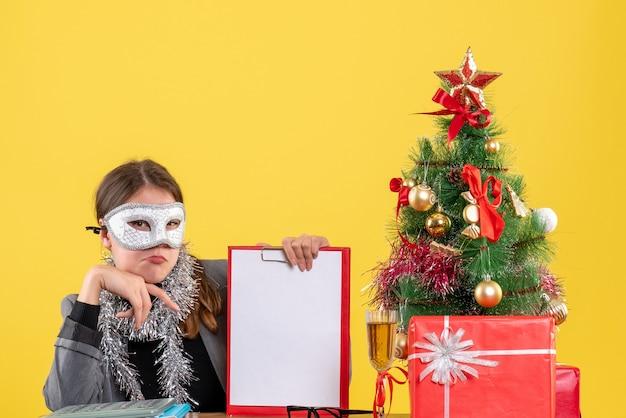 Nachdenkliches junges mädchen der vorderansicht mit maske, die am tischweihnachtsbaum und geschenkcocktail sitzt