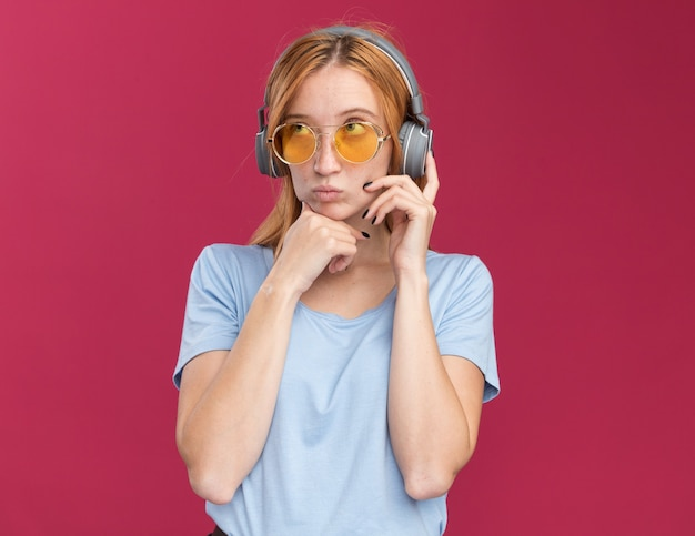 Nachdenkliches junges rothaariges ingwermädchen mit sommersprossen in sonnenbrillen und auf kopfhörern, die das kinn halten, isoliert auf rosa wand mit kopierraum