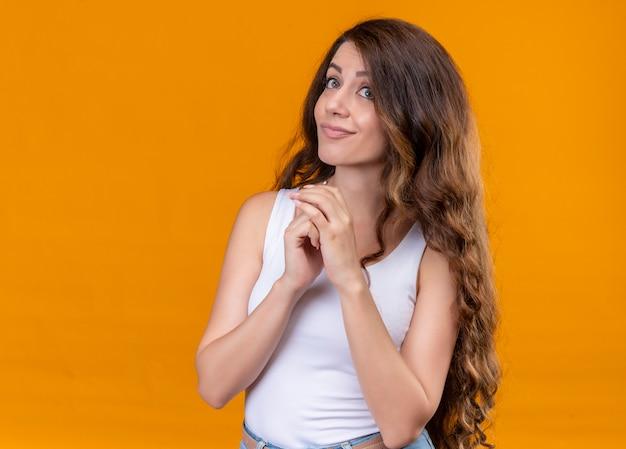 Nachdenkliches junges schönes mädchen, das hände zusammen auf isolierte orange wand mit kopienraum setzt