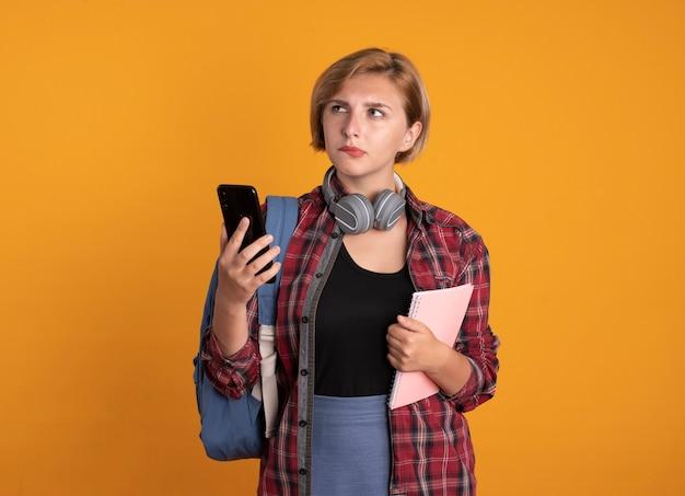 Nachdenkliches junges slawisches studentenmädchen mit kopfhörern, das rucksack trägt, hält notebook und telefon, das auf die seite schaut