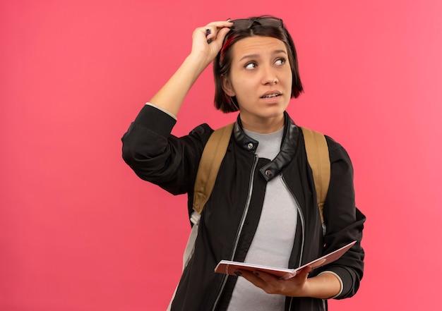 Nachdenkliches junges studentenmädchen, das brille auf kopf- und rückentasche hält, die notizblock und brille hält, die seite lokalisiert auf rosa wand betrachten