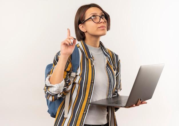 Nachdenkliches junges studentenmädchen, das brille und rückentasche hält laptop hält und lokalisiert auf weißer wand zeigt