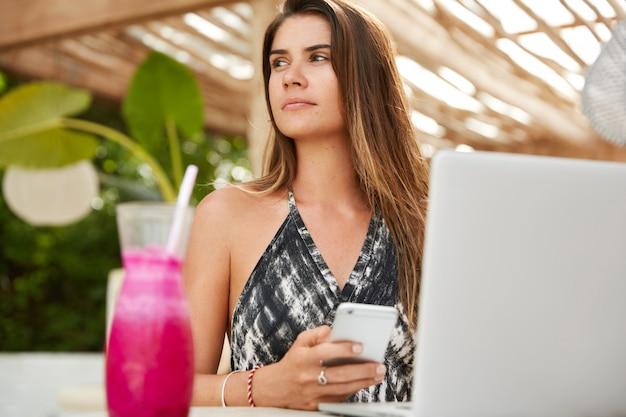 Nachdenkliches junges weibliches modell, das tief in gedanken ist, hält modernes smartphone