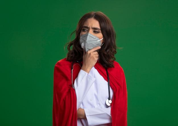 Nachdenkliches kaukasisches superheldenmädchen in der arztuniform mit rotem umhang und stethoskop, die medizinische maske tragen