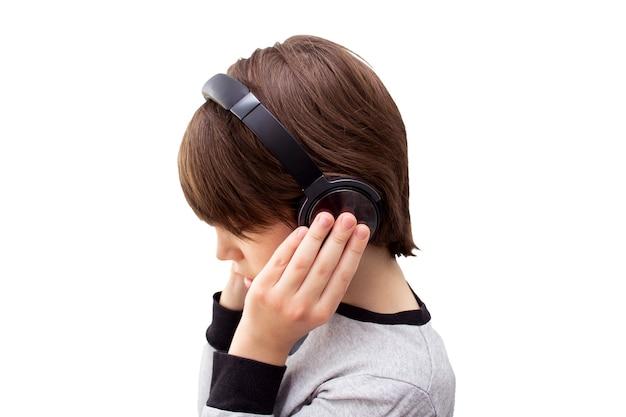 Nachdenkliches kind, das mit kopfhörern hört und nach unten schaut. isoliert auf weißem hintergrund.
