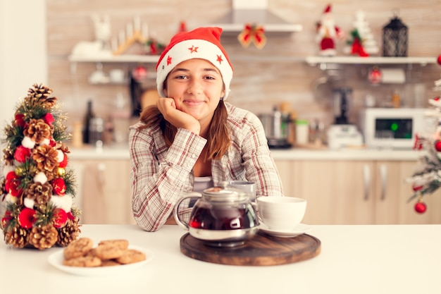 Nachdenkliches kind, das weihnachten und leckere kekse auf küchentisch und weihnachtsbaum genießt