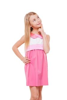 Nachdenkliches kind. fröhliches kleines mädchen in rosa kleid, das die hand am kinn hält und wegschaut, während es auf weiß isoliert ist