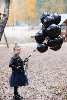 Nachdenkliches kind mit luftballons, die nach oben schauen
