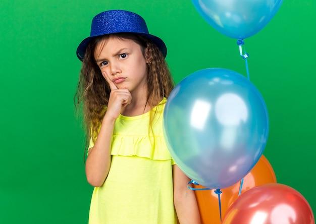 Nachdenkliches kleines kaukasisches mädchen mit blauem partyhut, das finger auf das kinn legt und heliumballons isoliert auf grüner wand mit kopienraum hält holding