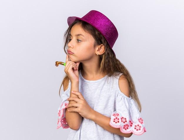 Nachdenkliches kleines kaukasisches mädchen mit lila partyhut, das die hand auf das kinn legt und die partypfeife hält und die seite isoliert auf weißer wand mit kopierraum betrachtet