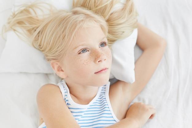 Nachdenkliches kleines mädchen mit blauen augen und langen wimpern, mit langen blonden haaren, seemanns-t-shirt tragend, auf weißem kissen liegend, beiseite schauend