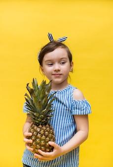 Nachdenkliches kleines sommermädchen hält eine ananasfrucht an einer gelben wand mit platz für text