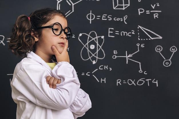 Nachdenkliches kleines wissenschaftlerin im laborkittel