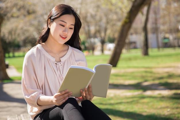 Nachdenkliches lächelndes hochschulmädchen, das lehrbuch studiert