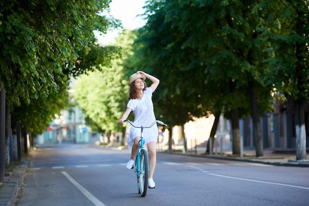 Nachdenkliches mädchen fährt auf der straße auf einem retro-fahrrad, das aufschaut und ihren hut auf ihrem kopf hält. sonniger sommertag