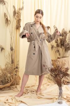 Nachdenkliches mädchen im beigen regenmantel auf pastellfarbenem stoffhintergrund. mode-fotoshooting