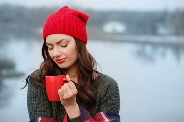 Nachdenkliches mädchen im freien trinkt kaffee