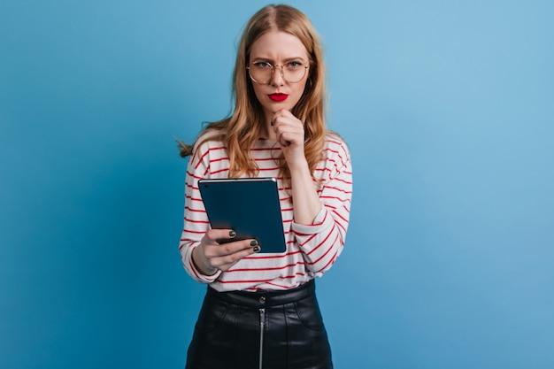 Nachdenkliches mädchen in den gläsern, die digitales tablett halten. studioaufnahme der blonden dame unter verwendung des gadgets auf blauem hintergrund.