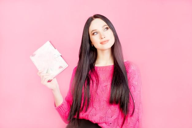 Nachdenkliches mädchen mit einem notizblock, auf einem rosa hintergrund. das konzept der geschäftsfrau oder der planung von frauenangelegenheiten, das leben eines mädchens.