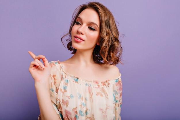 Nachdenkliches mädchen mit trendigem make-up, das weg schaut auf lila hintergrund