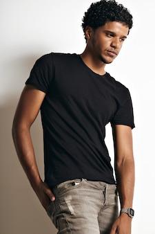 Nachdenkliches muskulöses schwarzes junges model in einem schlichten schwarzen baumwoll-t-shirt und jeans mit der rechten hand in der hinteren jeanstasche an der weißen wand.