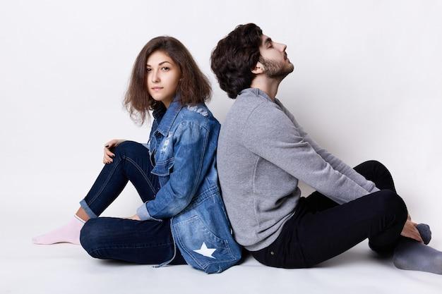 Nachdenkliches paar, das auf dem boden sitzt und sich ausruht. eine junge frau in jeanskleidung und ein stilvoller mann in freizeitkleidung