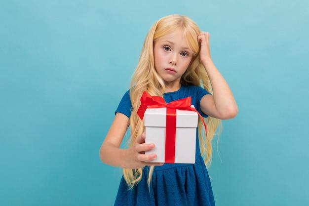 Nachdenkliches reizend blondes mädchen in einem kleid mit einem geschenk in ihren händen auf einem hellblauen