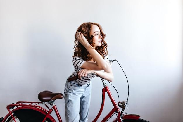 Nachdenkliches rothaariges weibliches modell, das mit fahrrad aufwirft. innenaufnahme der attraktiven lockigen frau, die neben fahrrad steht.