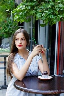Nachdenkliches schönes mädchen im straßencafé, das kaffee mit muffin trinkt