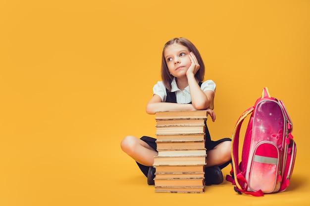 Nachdenkliches schulmädchen, das hinter einem stapel büchern mit rucksackkonzept des lernens und der schule sitzt