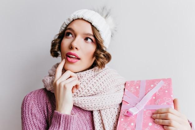 Nachdenkliches spektakuläres mädchen im niedlichen hut, der mit rosa geschenkbox aufwirft. ekstatische frau trägt einen gestrickten schal, der an etwas denkt und neujahrsgeschenk hält.