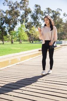 Nachdenkliches studentenmädchen, das smartphone verwendet