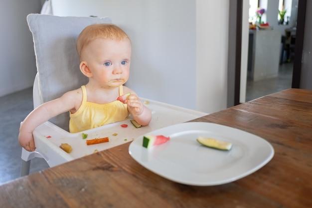 Nachdenkliches süßes baby, das stück wassermelone versucht, während im hochstuhl mit essen unordentlich auf tablett und gesicht sitzt. erstes konzept für feste lebensmittel oder kinderbetreuung