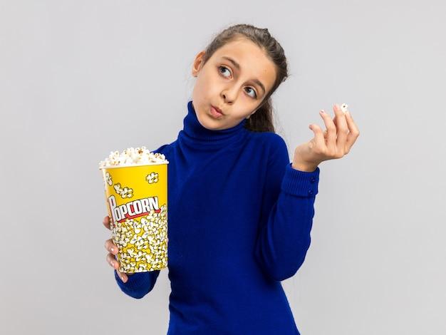Nachdenkliches teenager-mädchen, das eimer mit popcorn und popcornstück hält und mit geschürzten lippen auf die seite schaut, isoliert auf weißer wand
