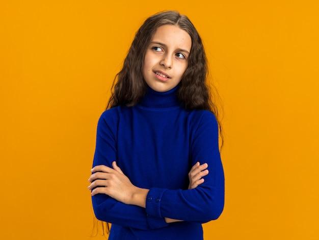 Nachdenkliches teenager-mädchen, das mit geschlossener haltung steht und auf die seite isoliert auf oranger wand mit kopierraum schaut
