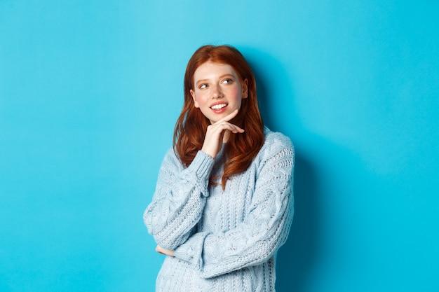 Nachdenkliches teenager-mädchen mit roten haaren, das logo in der oberen rechten ecke schaut und denkt, sich etwas vorstellt, auf blauem hintergrund steht