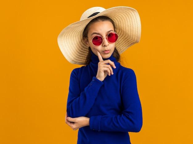 Nachdenkliches teenager-mädchen mit sonnenbrille und strandhut, das die wange mit dem finger berührt, der die kamera isoliert auf der orangefarbenen wand mit kopienraum betrachtet