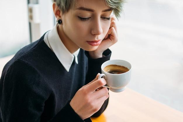 Nachdenkliches trauriges nachdenkliches junges mädchen, das eine tasse kaffee hält. frau mit emotionalem stress oder liebesdrama-konzept
