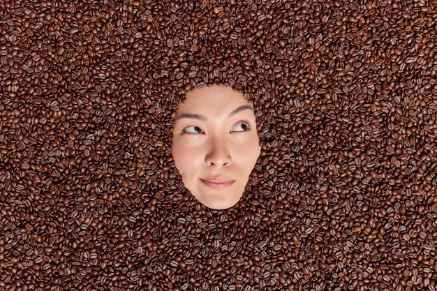 Nachdenkliches weibliches model, das in braunen kaffeebohnen ertrunken ist, sieht nachdenklich weg, verwendet geröstete samen, um ein erfrischendes getränk zuzubereiten, um die energie zu steigern oder ein hautpeeling mit einem angenehmen duft zu machen