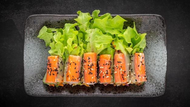 Nachgemachte krabbenstäbchen-salatrolle mit gemischtem bio-gemüse mit sesam auf dunklem texturhintergrund, draufsicht, gesundes essen, volles hd-verhältnis