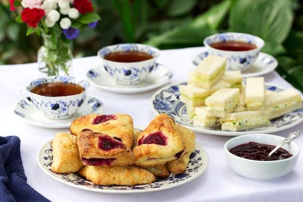 Nachmittagstee im garten mit scones, erdbeermarmelade, fingersandwiches mit gurken- und eiersalat.