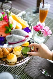 Nachmittagstee mit mini-brioche-häppchen. schöne englische nachmittagsteezeremonie mit desserts und snacks auswahl an süßigkeiten